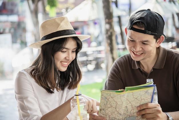 Casal asiático gosta de viajar sentado na cafeteria