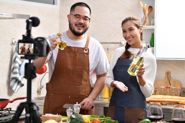 Casal asiático gravando um vídeo na cozinha