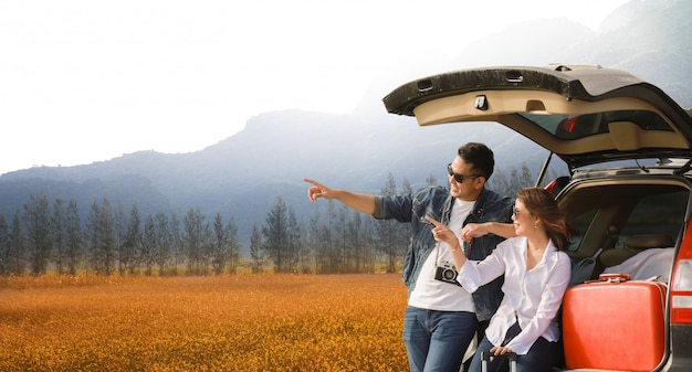 Casal asiático homem com camerra vintage e mulher sentada na traseira do carro