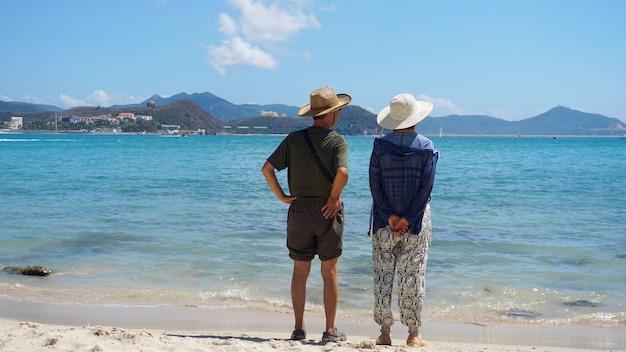 Casal asiático, homem e mulher com chapéus, ficam na praia à beira-mar e desviam o olhar