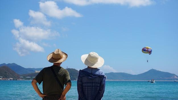 Casal asiático, homem e mulher com chapéus, ficando na praia à beira-mar e olhando o balão quente no céu