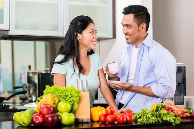 Casal asiático, homem e mulher, cozinhando comida juntos na cozinha e fazendo café