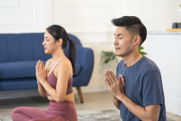 Casal asiático, homem e mulher, praticando ioga e meditando em casa