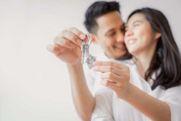 Casal asiático mostrando chave para nova casa