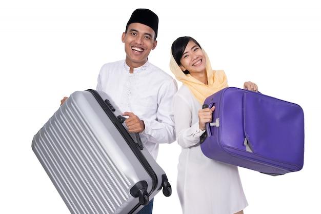 Casal asiático muçulmano com mala de viagem