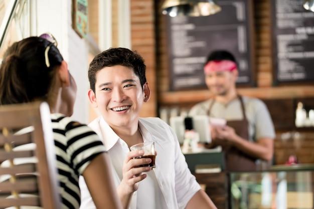 Casal asiático, mulher indonésia e homem coreano, flertando em um café enquanto bebe café