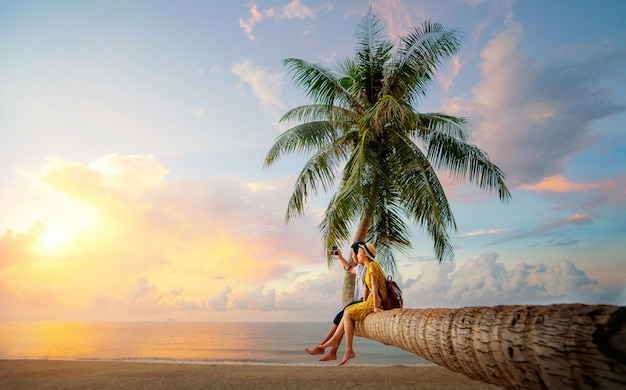 Casal asiático na palmeira de coco na ilha kho mak