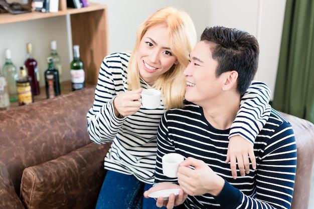 Casal asiático no sofá tomando café juntos
