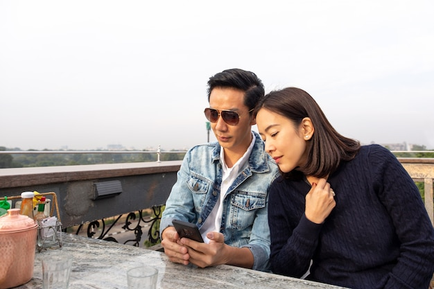Casal asiático olhando para celular no café ao ar livre.