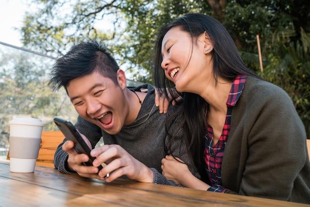 Casal asiático, olhando para o telefone móvel.