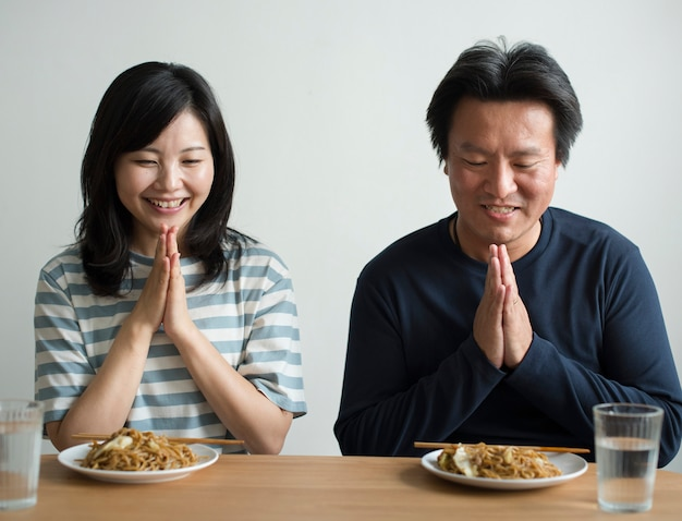 Casal asiático prestes a comer macarrão