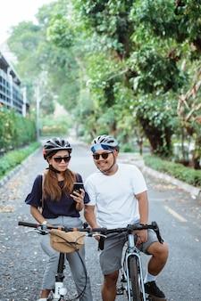 Casal asiático que usava capacete com telefone celular parecia feliz em andar de bicicleta juntos