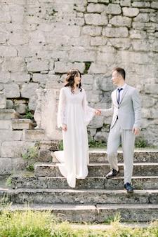 Casal asiático recém-casado romântico posando nas ruínas de um antigo castelo, de mãos dadas e em pé nas escadas de pedra