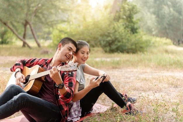 Casal asiático recostado um no outro, um homem tocando violão, uma mulher cantando em seus telefones celulares, ambos no parque.