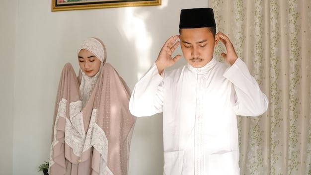 Casal asiático rezando juntos em casa