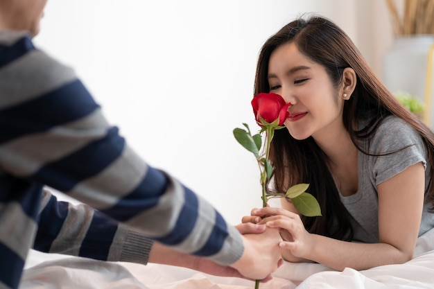 Casal asiático romântico no quarto, um homem dando uma rosa para uma linda mulher e os dois beijando uma linda rosa com amor e felicidade, lindo casal asiático elegante está abraçando e sorrindo no quarto