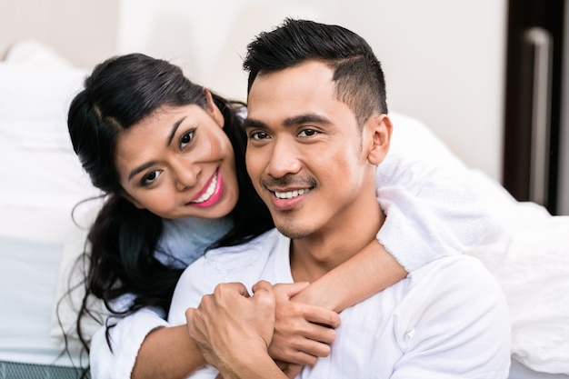 Casal asiático se abraçando na cama