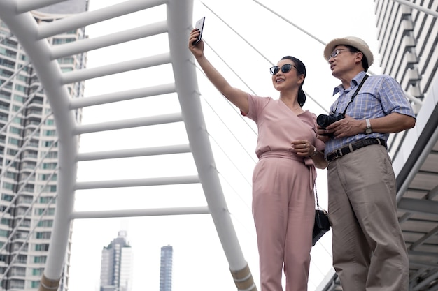 Casal asiático sênior em pé selfie pelo celular ao ar livre durante o dia, durante uma viagem juntos em um marco histórico na tailândia. conceito de viagens do casal sênior.