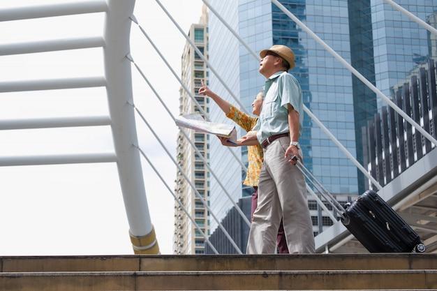 Casal asiático sênior está andando, arrastando sua bagagem e segurando um mapa para navegar pelas ruas da cidade grande