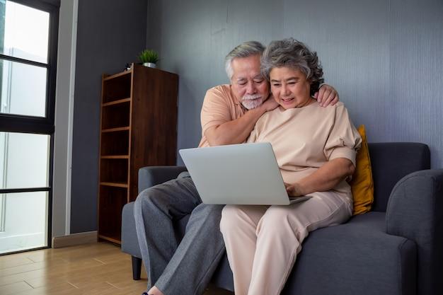 Casal asiático sênior, falando em vídeo chamada bate-papo no computador portátil, tecnologia inteligente para a velhice e ativismo on-line, ficar conectado conceito