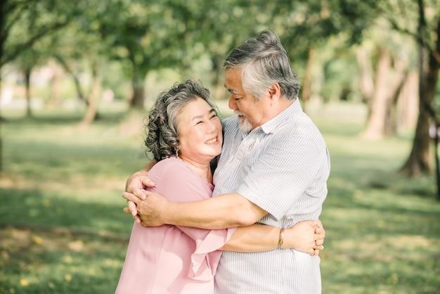 Casal asiático sênior feliz se divertindo, abraçando e se abraçando ao ar livre no parque