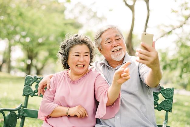 Casal asiático sênior rindo e sorrindo juntos enquanto olha para smartphone