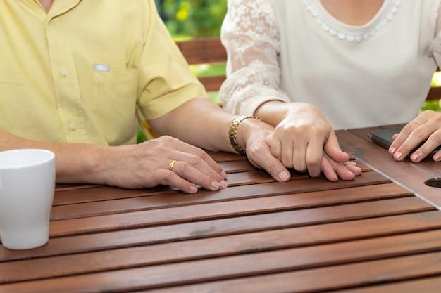 Casal asiático sênior, segurando a mão.