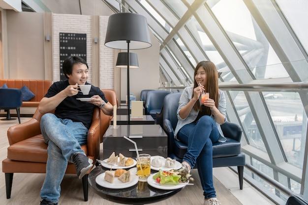 Casal asiático sentado e comendo no saguão do aeroporto enquanto espera o voo