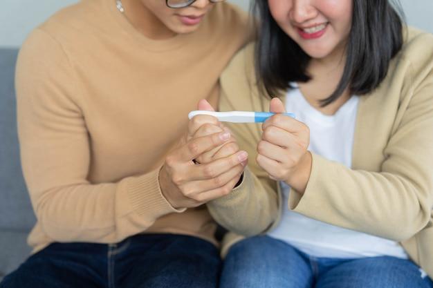 Casal asiático sentado no sofá enquanto se sente animado após olhar o teste do kit de gravidez