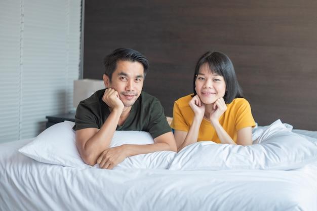 Casal asiático sorrindo e olhando a câmera na cama branca em casa