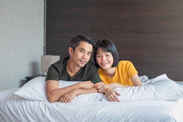 Casal asiático sorrindo e olhando juntos na cama branca em casa
