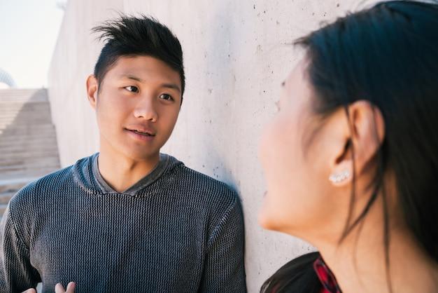Casal asiático tendo uma conversa.