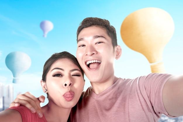 Casal asiático tirando uma selfie com um balão de ar colorido voando com o fundo da cidade