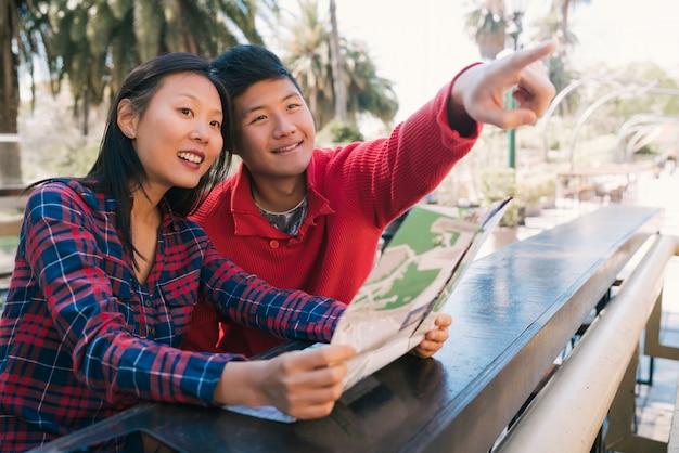Casal asiático viajante segurando um mapa e procurando instruções.