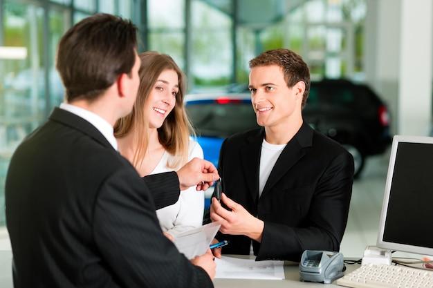 Casal assinando contrato de venda no concessionário automóvel