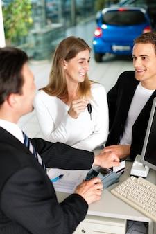 Casal assinando contrato de vendas no negociante de carro