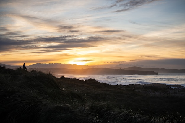 Casal assistindo a uma bela paisagem ao pôr do sol na praia de valdearenas em liencres, cantábria.