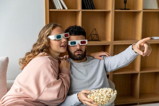 Casal assistindo filme em casa com óculos tridimensionais e comendo pipoca
