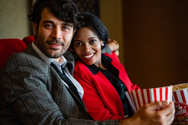 Casal assistindo filme, sentindo-se feliz e relaxando no cinema