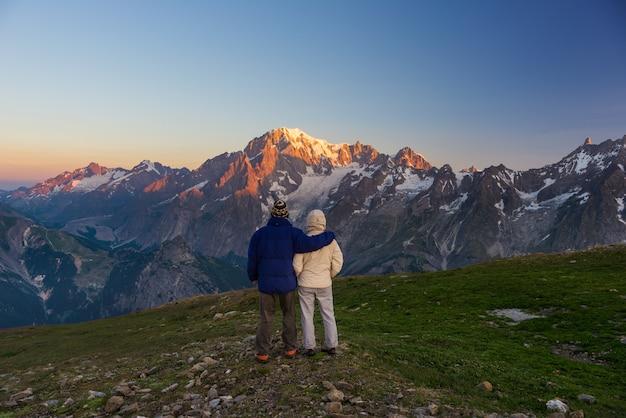 Casal assistindo o nascer do sol sobre o cume do mont blanc