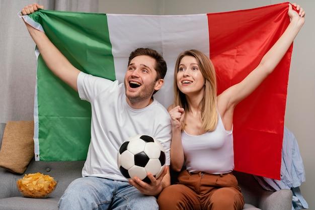 Casal assistindo programa de esporte na tv