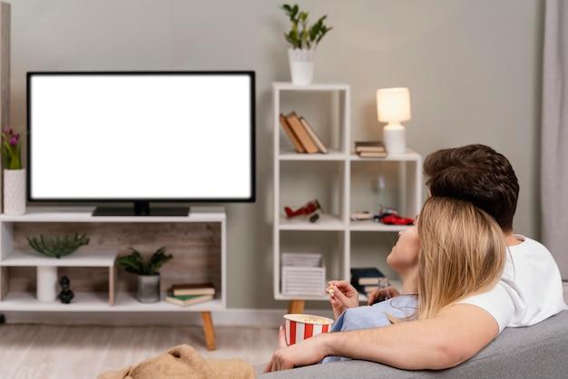Casal assistindo tv e comendo pipoca