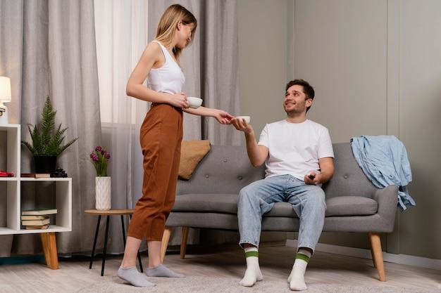 Casal assistindo tv e tomando café