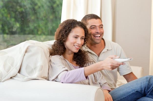 Casal assistindo tv em sua sala de estar em casa