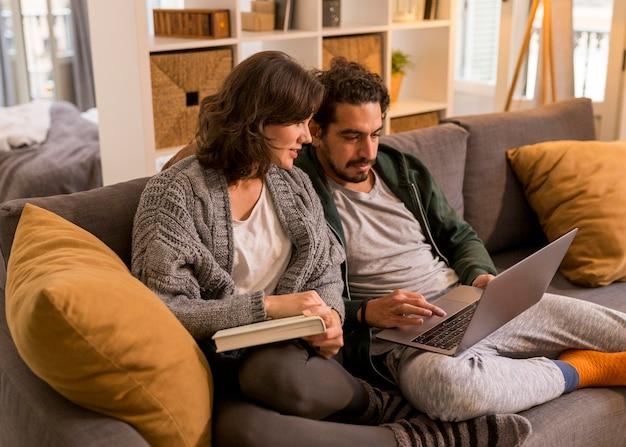 Casal assistindo um programa de tv na sala de estar