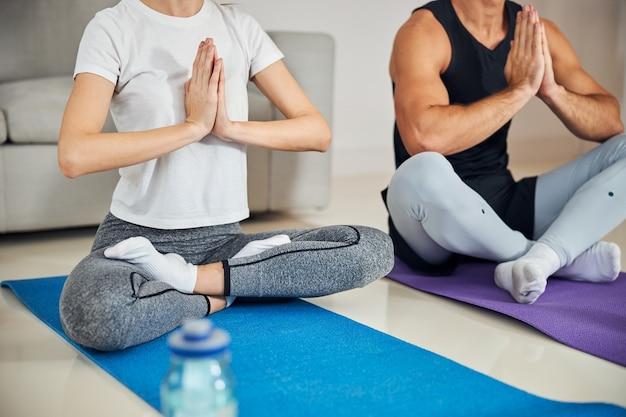 Casal atento fazendo meditação pós-treino em casa
