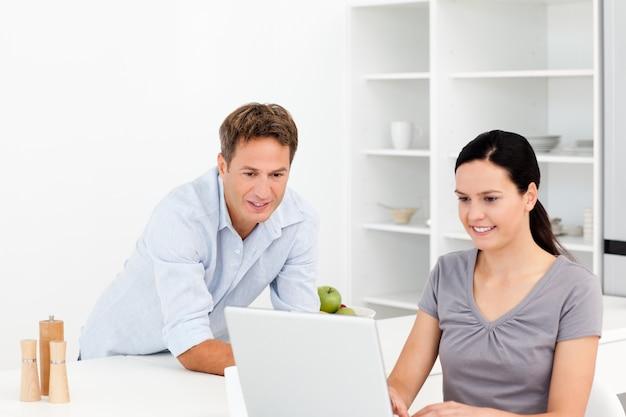 Casal atento trabalhando juntos no laptop na cozinha