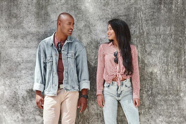 Casal atira jovem casal diverso em pé na rua da cidade na parede, olhando para cada um