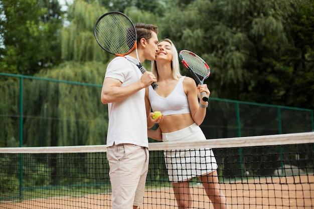 Casal ativo beijando na quadra de tênis