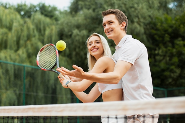 Casal ativo jogando tênis juntos
